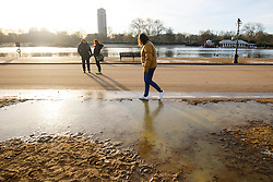 © Licensed to London News Pictures. 03/01/2017. London, UK. A woman walks over frozen puddles in Hyde Park, London on a frosty morning as temperatures in the capital drop below zero celsius on Tuesday, 3 January 2017. Photo credit: Tolga Akmen/LNP