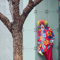 A clown takes cover from the rain at the Third Street Promenade on Sunday, March 1, 2015.