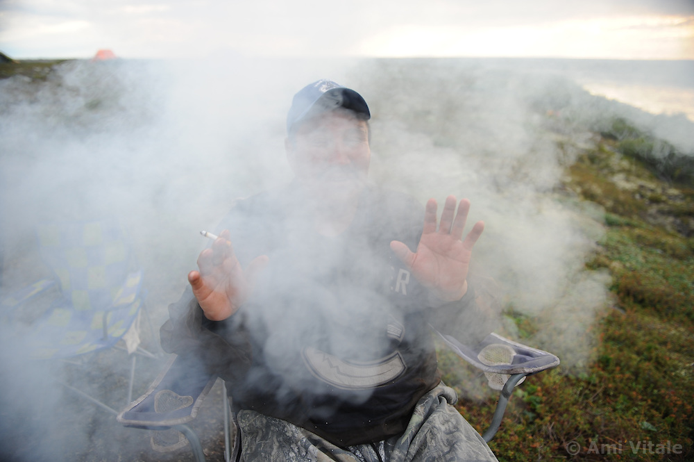 Dene First Nation James Lockheart sits in the smoke to get relief from mosquitoes in the Thelon Sanctuary August, 2011. It is a place ruled by the biggest and smallest--the grizzly and the mosquito--and by the extremes of sub-arctic seasons. The Thelon is the largest and most remote game sanctuary in North America, which almost no one has heard of. (Photo by Ami Vitale)