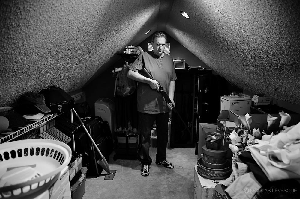Matt Knighten dans le grenier de son garage à son domicile. Il possède quatre pistolets et huit fusils à long canons. Il est armé à des fins d'auto-défense. Il cache sur lui un Glock 9mm qu'il emporte partout. Canton, USA.