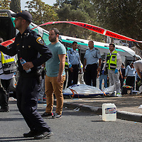 Israeli ZAKA emergency response members stand next to a body of an Israeli victim at the scene of a shooting attack in Jerusalem, Tuesday, Oct. 13, 2015. A pair of Palestinian men boarded a bus in Jerusalem and began shooting and stabbing passengers, while another assailant rammed a car into a bus station before stabbing bystanders, in near-simultaneous attacks that escalated a month long wave of violence. Two Israelis and one attacker were killed.<br />