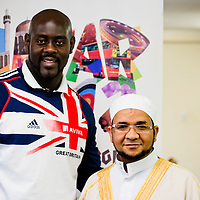 London, UK - 21 July 2012: Team GB Olympic discus thrower Abdul Buhari poses for a picture with Sheikh Khalifa Ezzat, Head Imam of the London Central Mosque (ICC) in Regents Park during the Ramadan Iftar 2012 celebrations