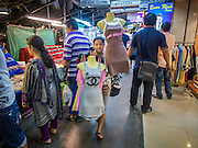 23 AUGUST 2014 - BANGKOK, THAILAND:        A woman walks through a night time market selling dresses on the sidewalk along Sukhumvit Road near Soi 5 in the Nana section of Bangkok. The Thai military junta, formally called the National Council for Peace and Order (NCPO), has ordered street vendors off of the sidewalks in an effort to bring order to Bangkok's chaotic sidewalks. Vendors have complained that the new regulations are hurting them economically but largely complied with the military orders.   PHOTO BY JACK KURTZ