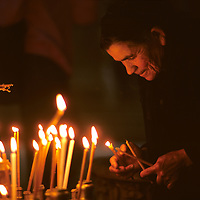 Israel, Jerusalem, Greek Orthodox Christian woman holds candles inside Church of the Holy Sepulcher on Easter morning