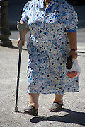 elderly woman using a crutch as a walking stick