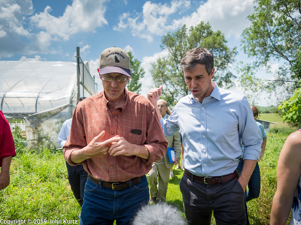 07 JUNE  2019 - LACONA, IOWA: MATT RUSSELL, left, co-owner of Coyote Run Farm, talks to BETO O'ROURKE while they tour Coyote Run Farm. O'Rouke toured Coyote Run Farm in Lacona Friday. He talked to Russell, the farm's co-owner, about the impact of President Trump's tariffs against China and proposed tariff's against Mexico on Iowa farmers and how climate change was changing American agriculture. O'Rourke, running to be the 2020 Democratic nominee for the US Presidency, has made climate change a central part of his campaign. Iowa traditionally hosts the the first selection event of the presidential election cycle. The Iowa Caucuses will be on Feb. 3, 2020.                               PHOTO BY JACK KURTZ