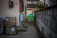 Soil contaminated by radioactive fall out from Fukushima Daiichi's March 2011 meltdown is stored almost out of sight under green plastic sheeting beside a Fukushima City home.  Fukushima, Japan.