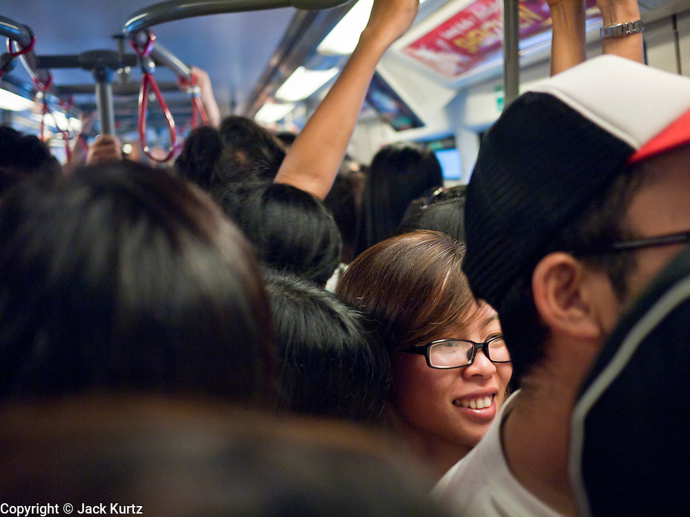 02 JULY 2011 - BANGKOK, THAILAND:   A woman riding the Sukhumvit line of the Bangkok Sky Train. The Bangkok Mass Transit System, commonly known as the BTS Skytrain, is an elevated rapid transit system in Bangkok, Thailand. It is operated by Bangkok Mass Transit System Public Company Limited (BTSC) under a concession granted by the Bangkok Metropolitan Administration (BMA). The system consists of twenty-three stations along two lines: the Sukhumvit line running northwards and eastwards, terminating at Mo Chit and On Nut respectively, and the Silom line which plies Silom and Sathon Roads, the Central Business District of Bangkok, terminating at the National Stadium and Wongwian Yai. The lines interchange at Siam Station and have a combined route distance of 55 km.    PHOTO BY JACK KURTZ