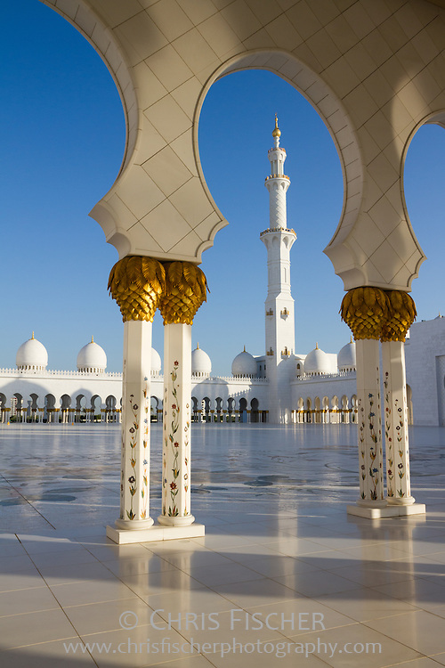 View of minaret across courtyard at the Sheikh Zayed Grand Mosque in Abu Dhabi, UAE.