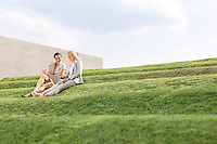 Young businesswomen using laptop together while sitting on grass steps against sky