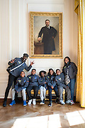Students and chaperones from Arthur Ashe Elementary in New Orleans wait under a portrait of Theodore Rooservelt before helping in the White House Kitchen Garden.