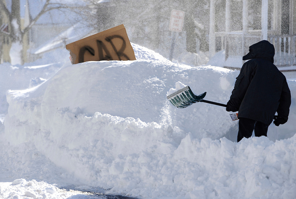 A boy digs around a car marked with a sign on a street in Windsor Locks, Conn. A behemoth storm packing hurricane-force wind gusts and blizzard conditions swept through the Northeast overnight. (AP Photo/Jessica Hill)