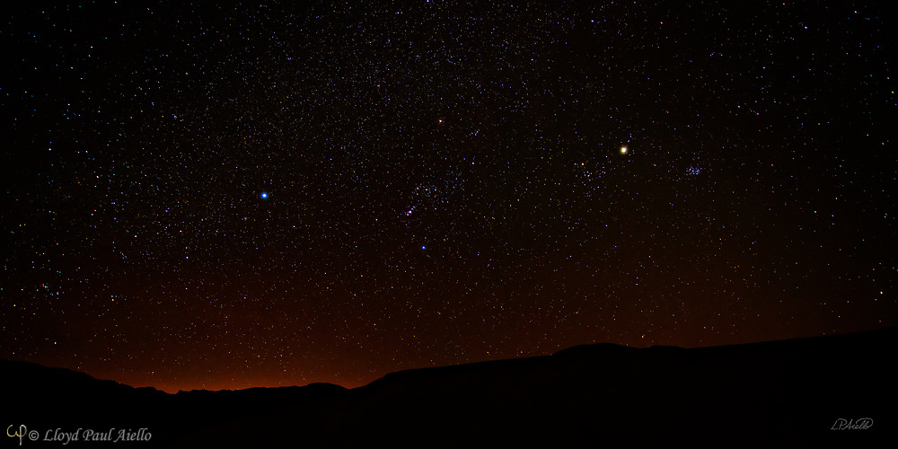 In the winter at Death Valley, the clear skies, cold nights and lack of nearby lights create one of the best viewing environments for the night sky.  Seen here in March, the many colors of the stars are clearly visible.  Centered in the image is the constellation Orion, with Orion&rsquo;s Belt and sword clearly visible.  Orion is observable worldwide in the evening sky from January to March.  It was named after Orion, a hunter in Greek mythology.  The earliest depiction of the constellation of Orion is a prehistoric (Aurignacian) mammoth ivory carving found in a cave in the Ach valley in West Germany in 1979. Archaeologists have estimated it to have been fashioned approximately 32,000 to 38,000 years ago<br /> <br /> Orion's Belt (or The Belt of Orion) consists of the three bright stars: Zeta (Alnitak), Epsilon (Alnilam), and Delta (Mintaka). Alnitak is approximately 800 light years away from earth and is 100,000 times more luminous than the Sun, although much of its radiation is in the ultraviolet range which the human eye cannot see. Alnilam is approximately 1,340 light years away from Earth and is 375,000 times more luminous than the Sun. Mintaka is 915 light years away and is 90,000 times more luminous than the Sun, and is a double star.  <br /> <br /> The Pleiades star cluster (also known as the Seven Sisters or M45) is visible from virtually every place on Earth and is one of the nearest star clusters. It can be seen from as far north as the north pole, and farther south than the southernmost tip of South America. It looks like a tiny misty dipper of stars, shown here 3/4 of the way to the right and halfway up in the sky.  In both myth and science, the Pleiades are considered sibling stars. The Pleiades stars were born from the same cloud of gas and dust about 100 million years ago. The cluster of several hundred stars is about 430 light-years distant, and the sibling stars drift through space together at about 25 miles per second. Many of these Pleiades stars