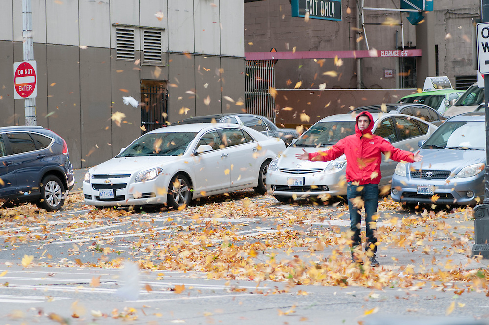 A man enjoys a storm of twirling leafs