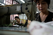 Two women work at sewing machines in a factory making clothing for export in Hangzhou.