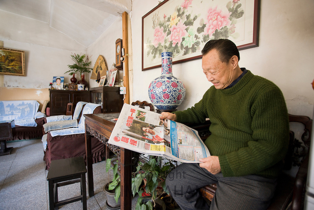 Man reads a newspaper story about the Beijing Olympic Games, in his home in the Hutongs area, Beijing, China