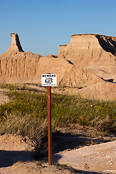 Rattlesnake warning sign along a hiking trail, Badlands National Park, South Dakota, United States of America