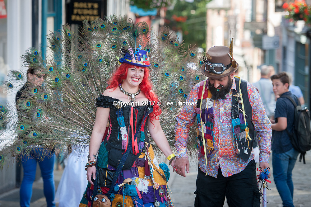 "Lincoln, Lincolnshire, UK. 26th August 2017. Pictured:  A couple walking up Steep Hill cause a sensation with fellow Steampunkers and onlookers alike. /  Thousands of people gather at what is claimed to be the ""largest steampunk event in the solar system"". The Asylum festival brings steampunkers from across the UK to Lincoln Castle and other historic parts of the city. Steampunk has been described as ""nostalgia for what never was"" and draws on a wide variety of influences from HG Wells to comics. About 35,000 to 40,000 people are expected to attend the event each day over the bank holiday weekend. // Lee Thomas, Tel. 07784142973. Email: leepthomas@gmail.com  www.leept.co.uk (0000635435)"