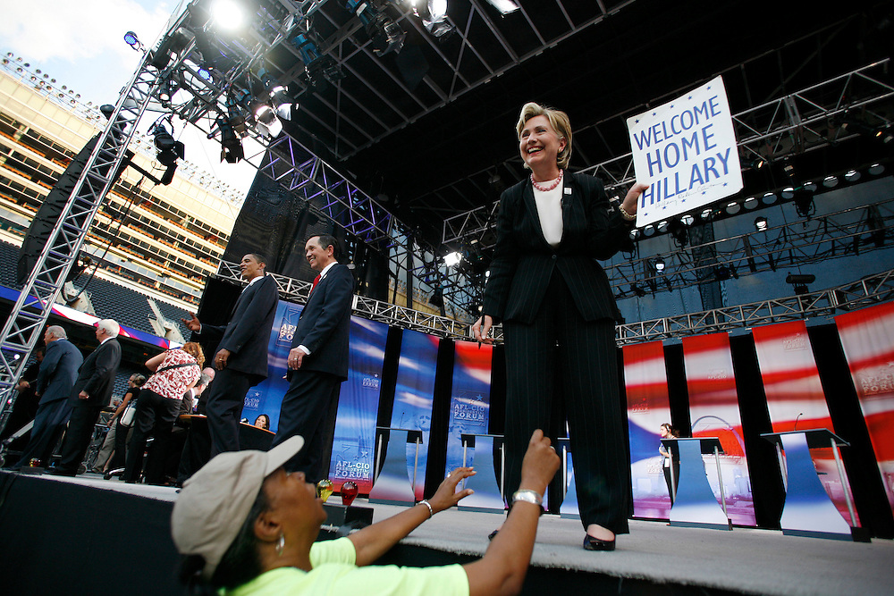 "Senator Hillary Rodham Clinton (D) of New York, a native of Park Ridge, Illinois, holds up a ""Welcome Home Hillary"" sign given to her by a supporter during a commercial break at an AFL-CIO Working Families Presidential Candidates Forum at Soldier Field in Chicago Tuesday evening."