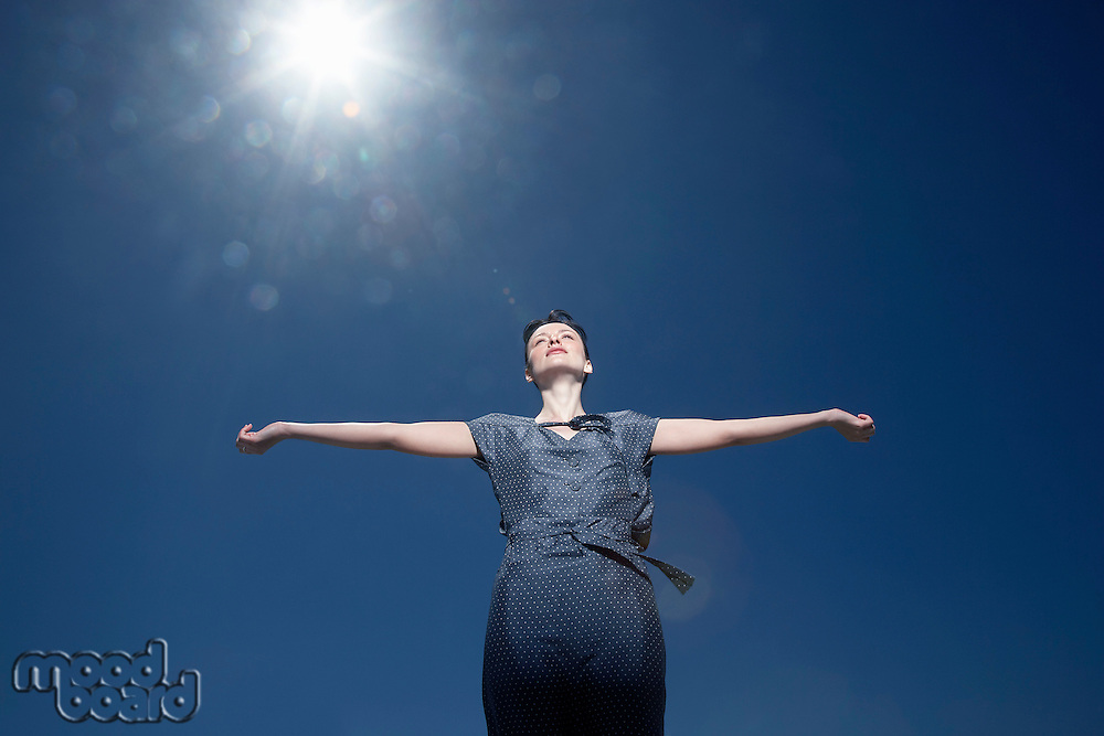 Woman with arms outstretched standing against sky low angle view