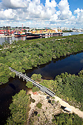 Aerial view of Port Everglades, container ship docking, bridge over waterway in foreground