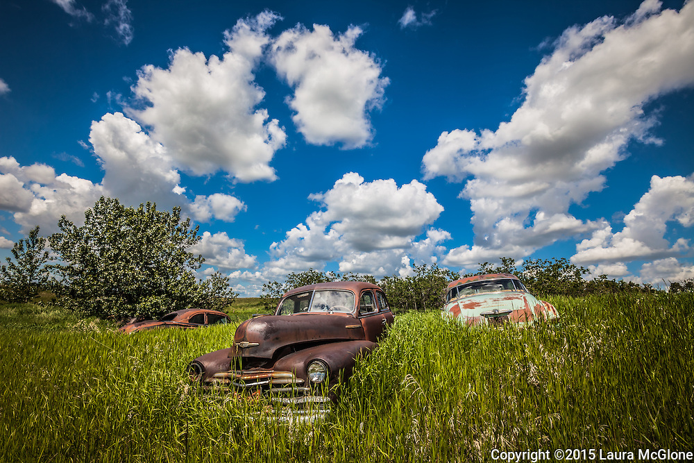 Car Graveyard of 1940s cars with dramatic clouds in summer, shot at angle