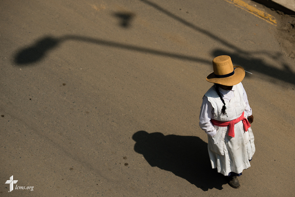 A woman wearing traditional clothing walks near the Noe (Spanish for Noah) school, one of many places affected by recent landslides near Lima, Peru, on Tuesday, April 7, 2015.  LCMS Communications/Erik M. Lunsford