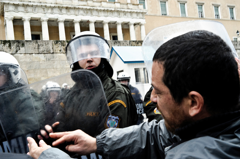 GREECE ATHENS FEBRUARY 7 2012 - Police officers in riot gear push back protesters. Minor clashes between protesters and police occurred during a demonstration against the storm of new austerity measures in response to the troika's demands, took place in central Athens under heavy rain on a 24-hour general strike called by labor unions.