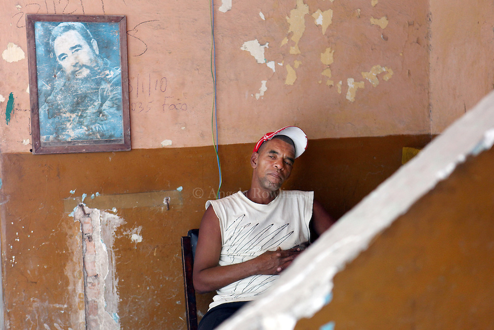 A man sits by a Fidel Castro poster in Barrio Chino, Wednesday,  April 28, 2010.