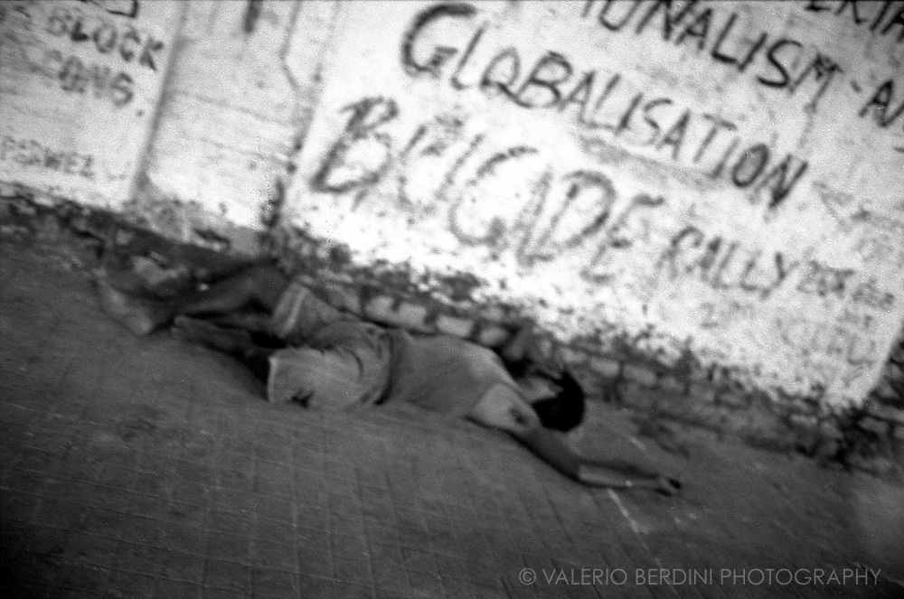 A men sleeps at night on a pavement in front of graffiti calling a political rally