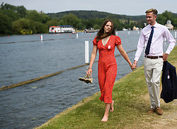 © Licensed to London News Pictures. 04/07/2018. Henley-on-Thames, UK. A woman walks with her shoes in her hand on day one of the Henley Royal Regatta, set on the River Thames by the town of Henley-on-Thames in England. Established in 1839, the five day international rowing event, raced over a course of 2,112 meters (1 mile 550 yards), is considered an important part of the English social season. Photo credit: Ben Cawthra/LNP