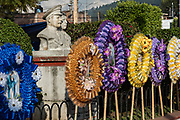 Colorful memorial wreaths on sale for the Day of the Dead festival next to statues of independence heroes in Plaza de Opopeo in Opopeo, Michoacan, Mexico.