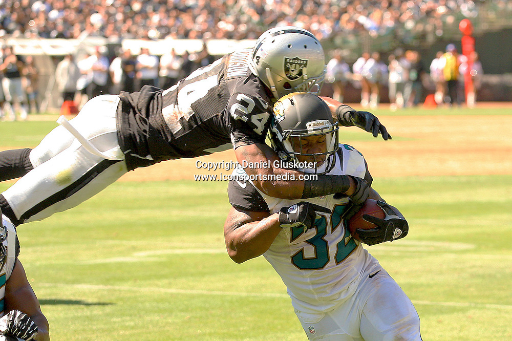 15 September 2013:  Raiders safety Charles Woodson takes down Maurice Jones-Drew during action in an NFL game against the Jacksonville Jaguars at O.co Coliseum in Oakland, CA. The Raiders posted a 19-9 victory over the Jags.