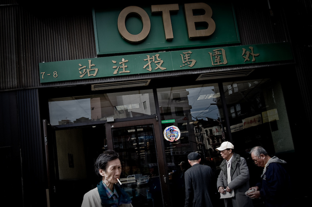 A group of men smoking outside an Off Track Betting branch in Manhattan, New York.  New York has three distinct Chinatowns, all are expanding.