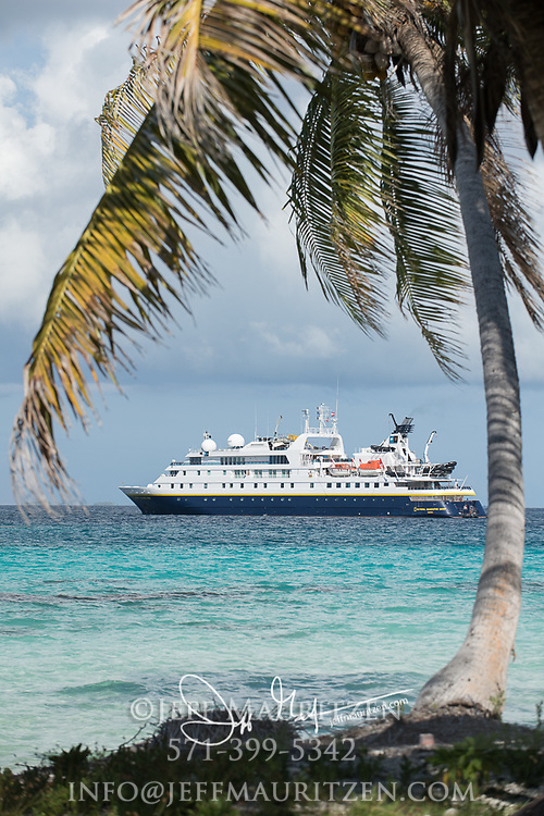 The National Geographic Orion expedition ship anchored off the coast of Raroia island, in the South Pacific.