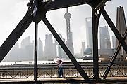 People walk across the Waibaidu Bridge over Suzhou River Shanghai, China