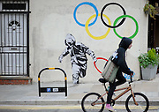 Graffiti by artist 'Pure Evil' appears on a wall in East London showing a man running off with one of  The Olympic Rings  7 August 2012..Ki Price.