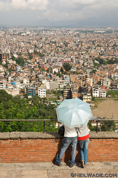 A young couple looks upon central Kathmandu from Swayambunath Stupa.