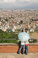 A young couple looks upon central Kathmandu from Swayambunath Stupa.