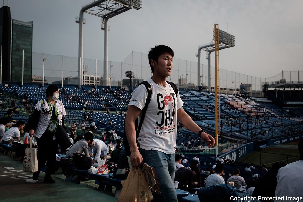 A Supporter of The Tokyo swallows looks for his seat at the Jingu Baseball Stadium in Tokyo before a game Tokyo Swallows VS Hiroshima Carp, Japan. 21/04/2017-Tokyo, JAPAN