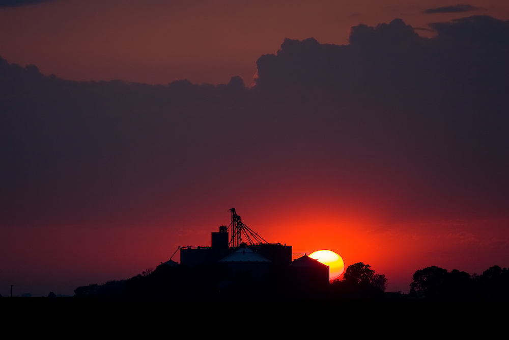 As summer thunderstorms gather on the horizon, the sun sets on the Illinois prairie, silhouetting a large grain elevator complex.