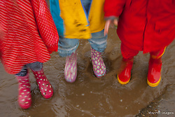 Children's rainboots in mud puddle