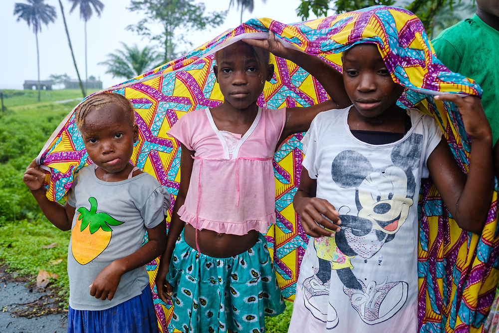 Children sheltering from the rain in São Tomé island