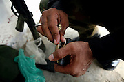 A member of the AVCC, (Anti-Violence Crime Cell) a special police unit mostly involved in anti-terrorism operations and kidnapping cases in the city of Karachi, is loading his Pakistani made G3 assault rifle in preparation of a night raid on the outskirts of the city searching for a kidnap suspect.
