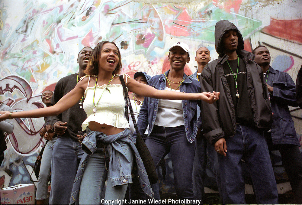 A  group of West Indians dancing and celebrating with giant sound system in the streets of Notting Hill at the time of  the carnival.