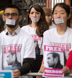 © London News Pictures. 02/11/2013.  London, UK. NANCY THORBURN (centre), girlfriend of imprisoned Greenpeace journalist  Kieron Bryan wearing a sticker over her mouth at a silent demonstration outside the Russian Embassy in London to protest against the arrest of Kieron Bryan and 30 Greenpeace activists, known as the 'Arctic 30' , following a peaceful protest against Arctic oil drilling at an oil platform in the Pechora Sea. Photo credit Ben Cawthra/LNP