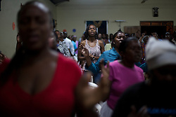People pray at the Palabra Viviente church on January 20, 2013  in Corozal, Honduras.  This church often preaches in Garifuna and uses traditional music during the church service. (David Rochkind/ Pulitzer Center)