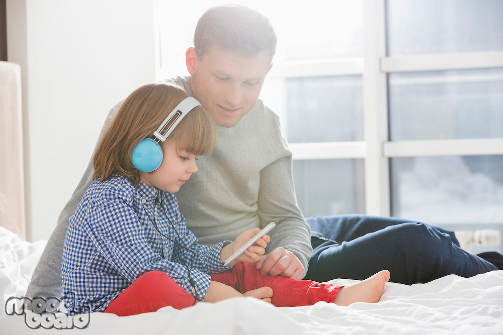Father with boy listening music on headphones in bedroom