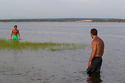 two shirtless men standing in shallow water looking at each other