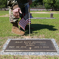 Staff Sgt. David Fetterman  finishes palcing a flag oj the grave of a veteran at Tupelo Memorial Park in Tupelo.